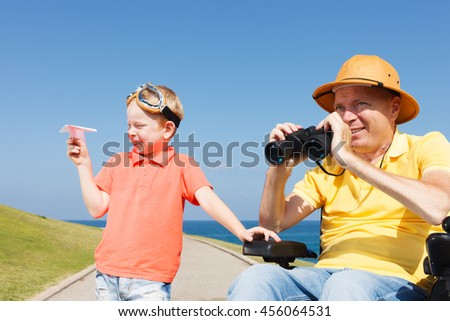 Disabled father looking through binoculars with boy playing with paper plane  - stock photo