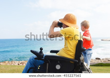 Disabled father looking through binoculars with his young boy