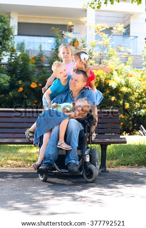 Disabled father with children having fun at the park - stock photo