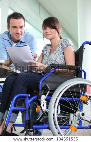 Disabled female office worked with colleague - stock photo