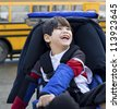 Disabled five year old boy in wheelchair, by school bus - stock photo