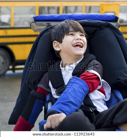 Disabled five year old boy in wheelchair, by school bus