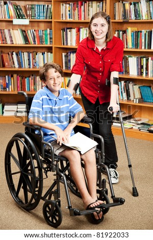 Disabled girl and boy in the school library. - stock photo
