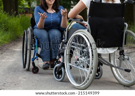 Disabled girls during conversation on the street - stock photo