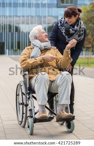 Disabled grandpa and granddaughter spending time outdoors - stock photo