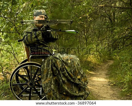 disabled hunter in wheelchair using a crossbow - stock photo