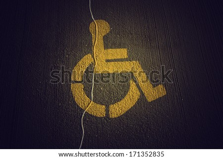 Disabled icon on broken asphalt background - stock photo
