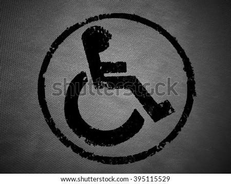 disabled icon sign, black old fabric background. - stock photo