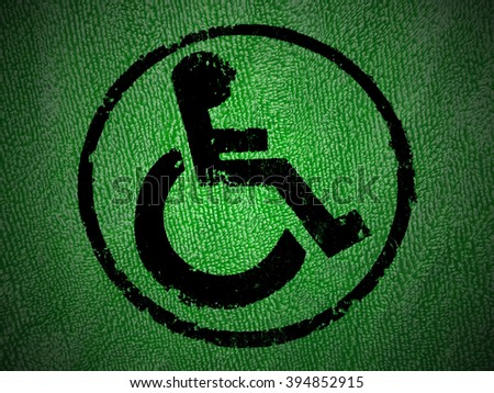disabled icon sign, green old fabric background. - stock photo
