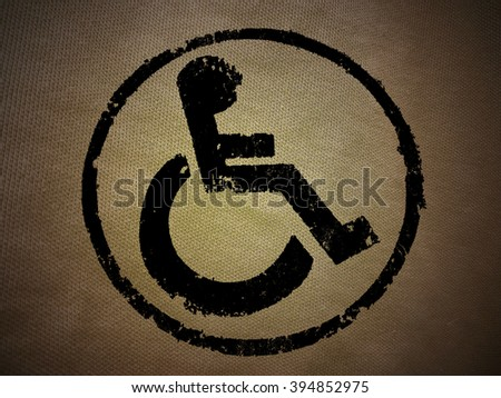 disabled icon sign, orange old fabric background. - stock photo