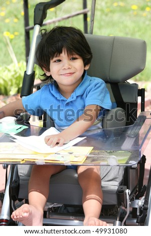 Disabled little boy in medical stroller or wheelchair
