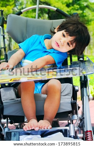 Disabled little boy in medical stroller or wheelchair. Head leaning to the side due to weak muscle tone. - stock photo