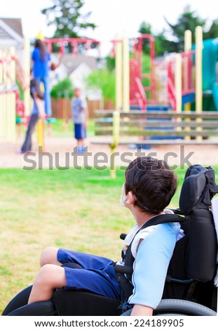 Disabled little boy in wheelchair sadly watching children play on playground - stock photo