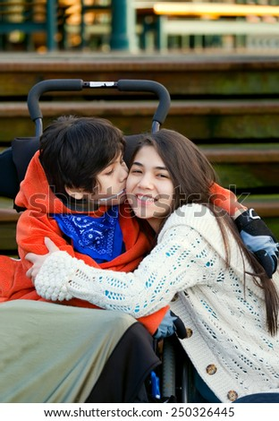 Disabled little boy kissing his big sister on cheek while seated in wheelchair - stock photo