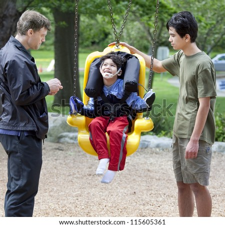 Disabled little boy swinging on special needs swing being pushed by family - stock photo