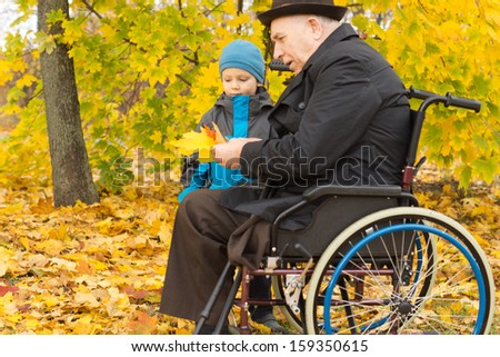 Disabled man and his grandson enjoying autumn playing together in colourful yellow woodland as the little boy brings fallen leaves to his grandfather in the wheelchair - stock photo