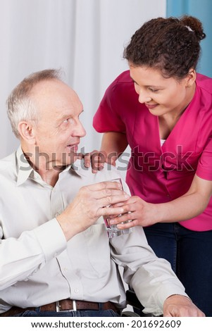Disabled man drinking water in a hospice - stock photo