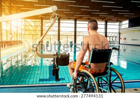 Disabled man in a swimming pool. Wheelchair. Disabled man in a wheelchair. - stock photo