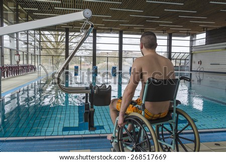 Disabled man in a swimming pool. Wheelchair. Disabled person in a wheelchair.