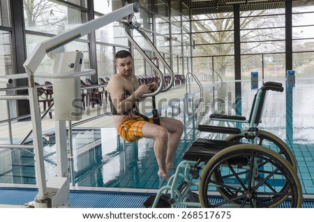 Disabled man in a swimming pool. Wheelchair. Disabled person in a wheelchair. - stock photo