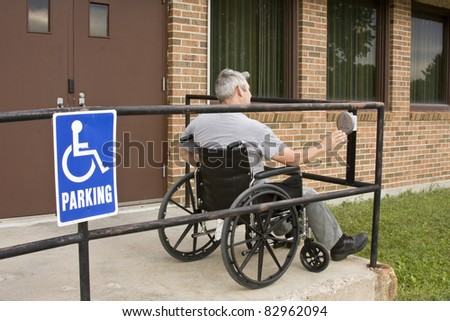 disabled man in a wheelchair pushing a handicapped entrance button - stock photo