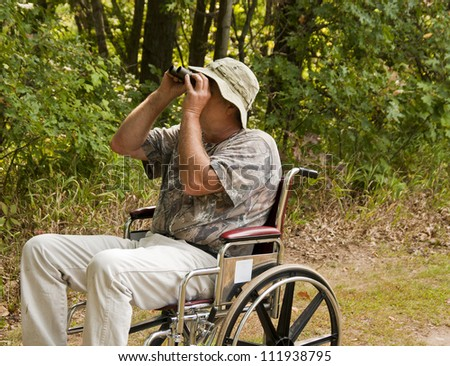 disabled man in a wheelchair watching for birds with a pair of binoculars - stock photo
