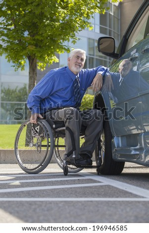 Disabled man in his wheelchair leaning on his accessible van - stock photo