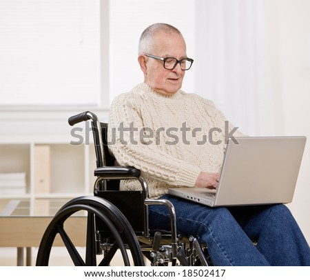 Disabled man in wheelchair typing on laptop - stock photo