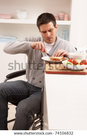 Disabled Man Making Sandwich In Kitchen - stock photo