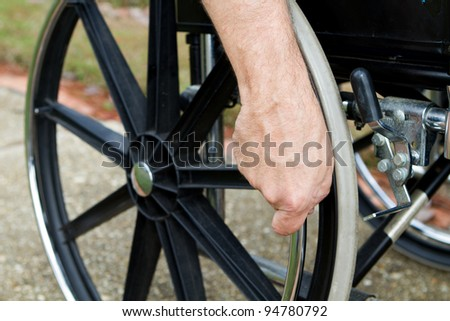 Disabled man's hand grips the push rim on his wheelchair. - stock photo
