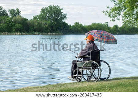 disabled man sitting in wheelchair by the lake fishing on a summer day - stock photo