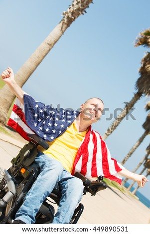 Disabled man sitting in wheelchair with flag of USA showing freedom - stock photo