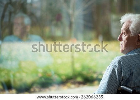 Disabled man suffering from loneliness in old age - stock photo