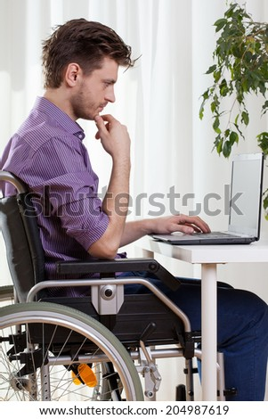 Disabled man using a laptop at home - stock photo