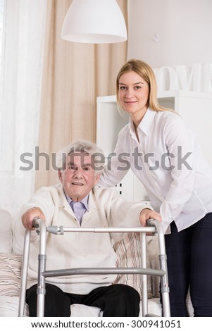 Disabled man using walking frame and assisted carer - stock photo