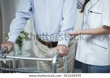 Disabled man using walking frame during rehabilitation - stock photo