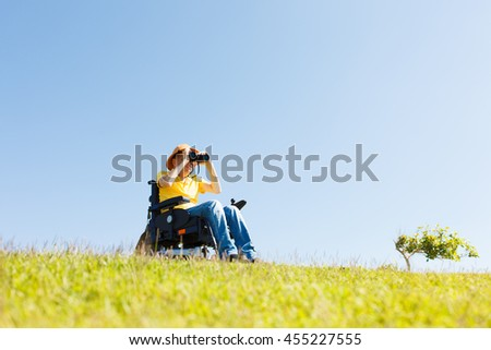 Disabled man with binocular sitting on the wheelchair  - stock photo