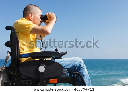 Disabled man with binocular sitting on the wheelchair. Sea on the background