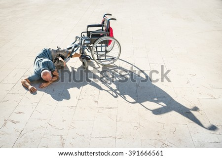 Disabled man with handicap having an accident crash with wheelchair - Disability concept with powerless unhelped person lying on the floor - Social issues with invalid guy on difficultes - stock photo