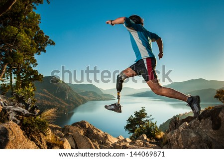 Disabled man with prosthetic leg, jumping in Patagonia. - stock photo
