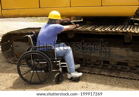 disabled man working on the tracks of a large backhoe - stock photo