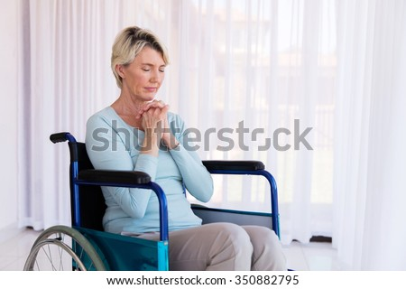 disabled middle aged woman sitting on wheelchair and praying - stock photo