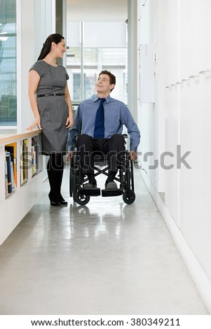 Disabled office worker with colleague - stock photo