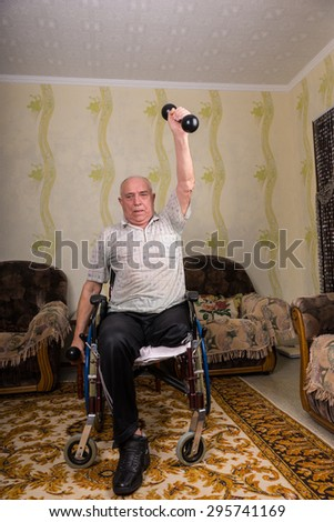 Disabled old men doing exercises with dumbbells - stock photo