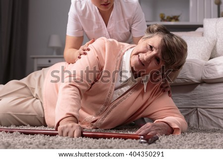Disabled older woman on floor and caring young assistant - stock photo