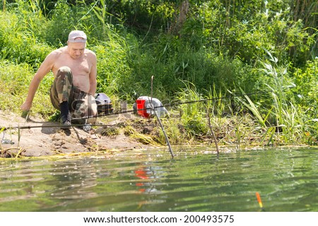 Disabled one legged fisherman adjusting his sitting position moving closer to the water of the lake or lagoon as he watches over his two fishing rods - stock photo