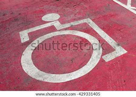 Disabled parking sign on the floor in red on a food center. - stock photo