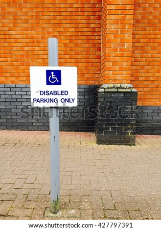 Disabled parking space sign sign on a pole warning motorists - stock photo