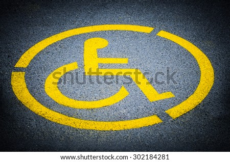 Disabled person parking place permit mark, traffic symbol on the asphalt road - stock photo