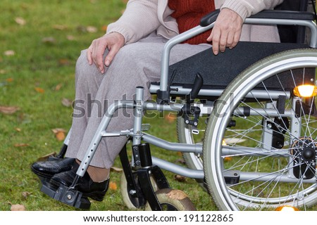 Disabled person sitting on wheelchair outdoors, horizontal - stock photo